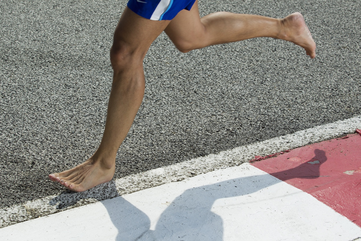 Closeup of a runners feet barefoot running